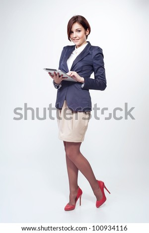 A full length portrait of a beautiful businesswoman standing with tablet - stock photo