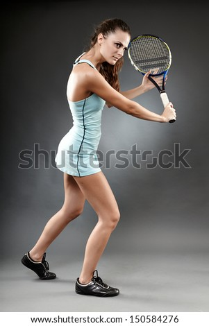 A full length studio shot of a female tennis player executing a backhand volley - stock photo