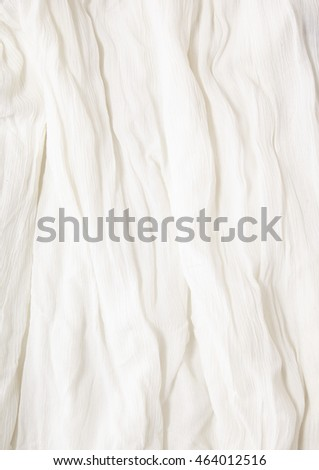 A full page close up of a ruffled, off white crape fabric texture