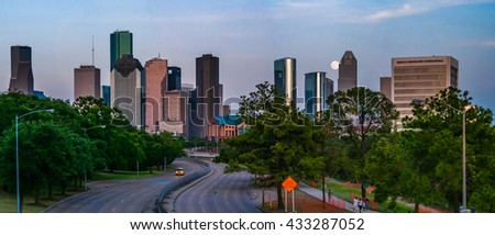 A full supermoon rising over Memorial Ave behind the Houston skyline in Houston, TX with all of the major Houston skyscrapers in view. - stock photo