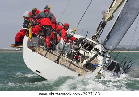 A fully crewed racing yacht racing hard and leaving a big wake - stock photo