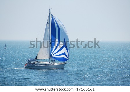 A fully crewed racing yacht with a blue and white spinnaker catching the wind - stock photo