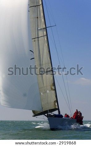 A fully crewed racing yacht with a white spinnaker catching the wind - stock photo