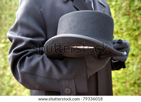 A funeral leader is respectfully carrying his hat - stock photo