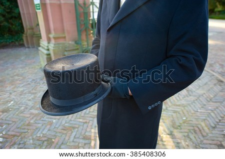 A funeral leader with a hat in his hands is waiting on a cemetery