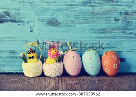 a funny couple of teddy chicks, a male and a female, and some different ornamented easter eggs on a wooden surface, against a blue rustic wooden background - stock photo