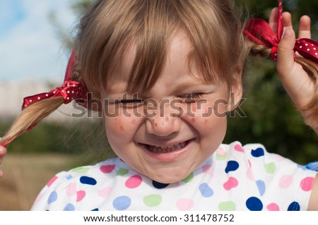 A funny cute outdoor close up portrait of a smiling little girl presenting Pippi Longstocking with her eyes closed and making faces   - stock photo