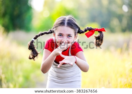A funny cute outdoor portrait of a little girl presenting Pippi Longstocking and showing out out her tongue.  - stock photo