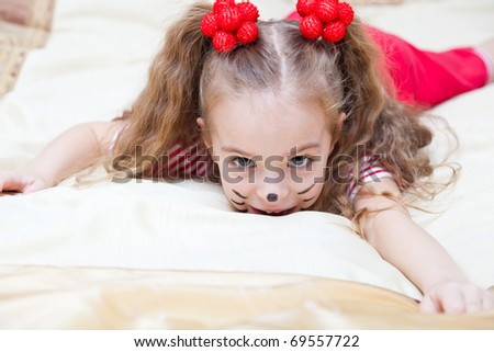 a funny girl is portraiting a kitten is lying on the bed