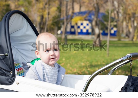 A funny little baby boy in a baby carriage - stock photo