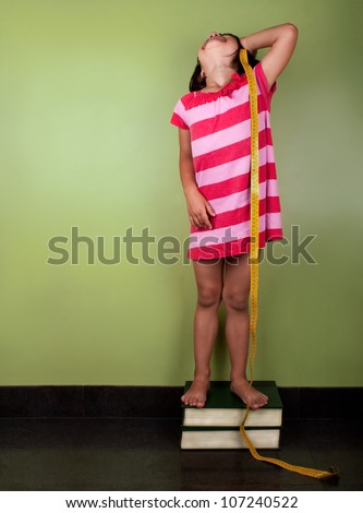 a funny little girl measuring herself with a yellow meter up in to books - stock photo