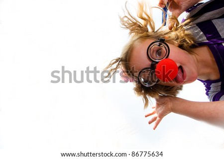 A funny little girl with a clown nose make a silly face looking down on the camera. - stock photo