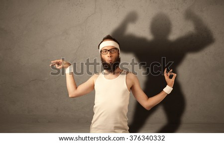 A funny young guy posing in front of brown background with musculous body shadow reflected on the wall  - stock photo