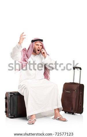 A furious arab shouting on a mobile phone seated on his luggage isolated on white background - stock photo