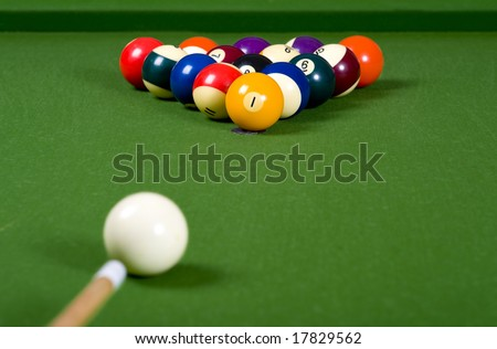 A game of pool with the balls lined up in an 8-ball formation on a green felt pool table - stock photo