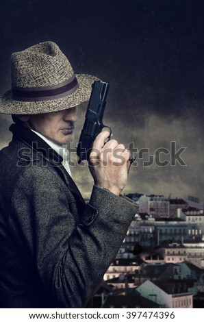 A gangster with hat holding a handgun with a city in the background - stock photo