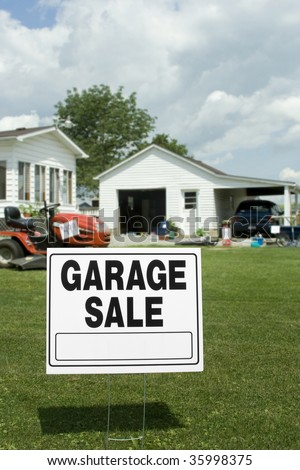 A garage sale sign with garage and items in background. Room for copy. - stock photo