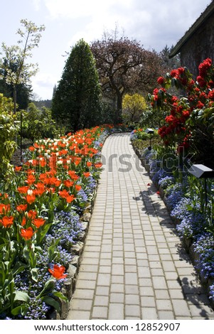 A garden footpath with beautiful blooming flowers in spring - stock photo