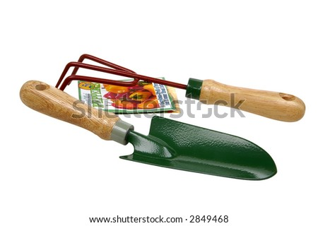 a garden hand cultivator and a hand rake with 1960s packages of seeds - stock photo