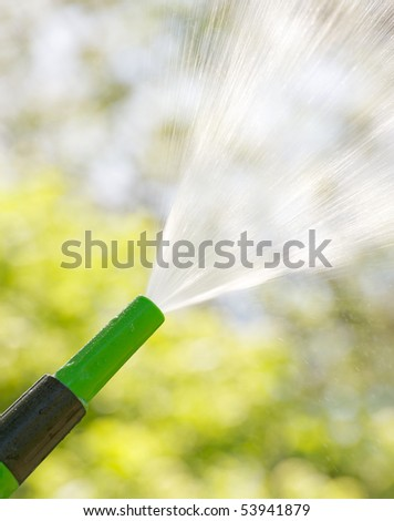 A garden hose sprays into the sunshine on a hot summer day. - stock photo