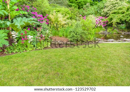 A garden scene with pink azaleas and a reflecting pool