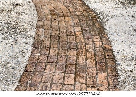 A garden walkway constructed of old bricks and mortar. - stock photo