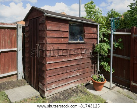 A garden wooden shed with planks in a  yard.