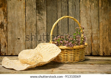 A gardener's straw hat and basket of freshly cut oregano and a aged barn board background. - stock photo