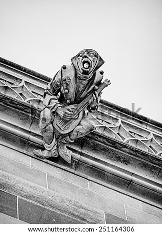 A gargoyle playing a mandolin serves as a downspout for rainwater coming from the roof of the Bern Minster cathedral in Switzerland. - stock photo