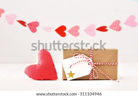 A garland of hearts above a small gift-wrapped box and red textile heart on a neutral white background - stock photo