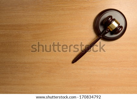 A gavel isolated  on a wood table - stock photo