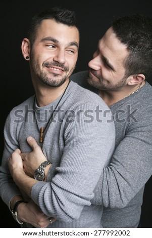 A gay couple on black background studio - stock photo
