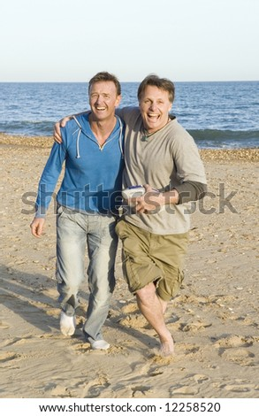 A gay couple running and laughing. - stock photo