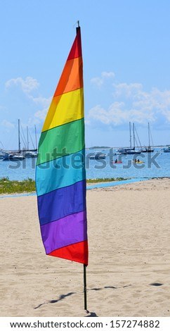 A gay pride feather flag against the background of a marina in Provincetown, Massachusetts
