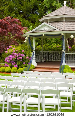 A gazebo and white chairs at a wedding venue for the ceremony and reception. - stock photo