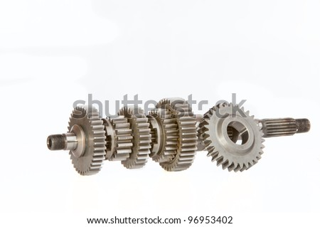 A gearbox main-shaft and with a single gear cog resting against it, shot in studio over a white background.