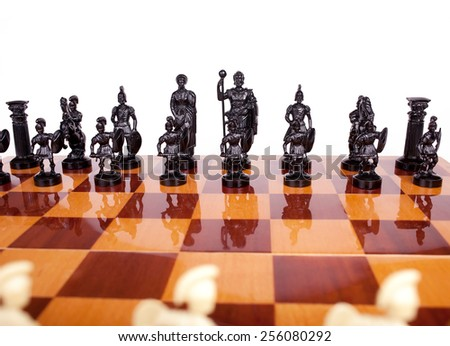 A general view of black chess pieces on a chessboard Romans at the beginning of a game of chess on a white background - stock photo