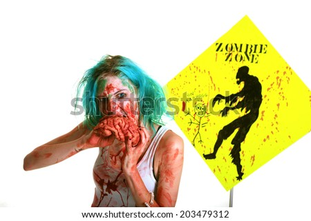 A genuine Female Zombie enjoys eating a Fresh Brain from her latest Victim. Zombies are currently the most popular monster in the entertainment field, even more than Vampires, Mummies, Aliens etc. - stock photo