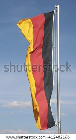 A German flag against a blue sky - stock photo