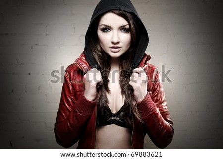 A ghetto styled girl posing in front of brick wall - stock photo