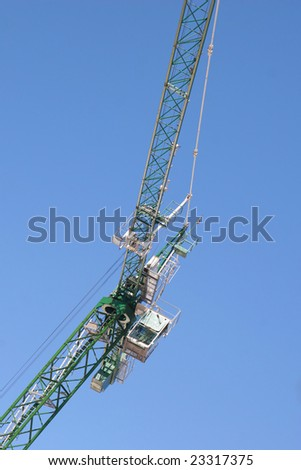 A giant construction crane with its cab and operator.