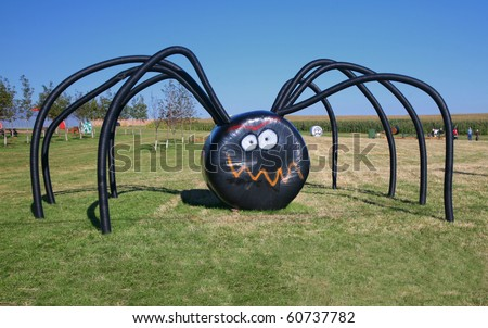 a giant halloween spider on the farm made of covered hay bales and irrigation tubing - Giant Halloween Spider
