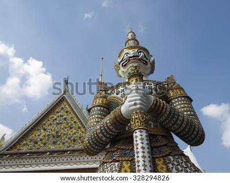 A giant porcelain guardian at the front of the Wat Arun temple in Bangkok , Thailand - stock photo