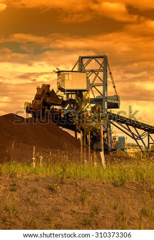 A giant wheel excavator in brown coal mine at sunset  - stock photo
