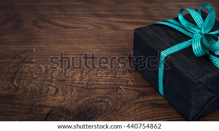 A gift box on wooden board with FOREVER water drop text. - stock photo