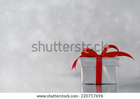 A gift box with closed lid, wrapped in metallic silver paper and tied to a bow with red satin ribbon.  Sparkling, star lit bokeh background. - stock photo