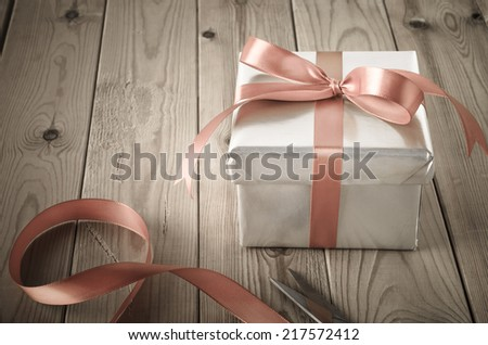 A gift box with closed lid, wrapped in silver paper and tied to a bow with a satin ribbon.  Placed on a weathered old wooden table with scissors and remains of cut ribbon.  - stock photo