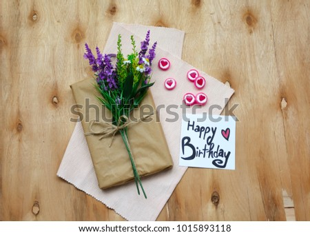 A Gift Box With Flowers And Happy Birthday Text On Note Rustic Wooden Table