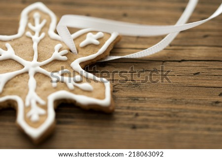 A Ginger Bread Star Cookie with white Decoration on Wood as Background with Copy Space - stock photo
