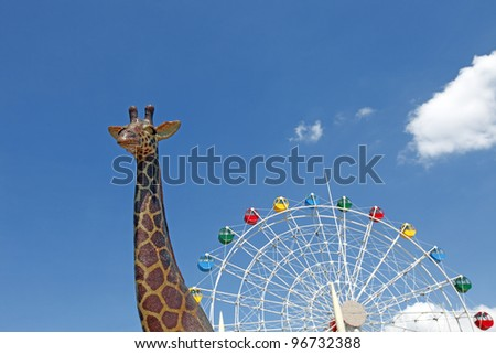 A giraffe with a ferris wheel in the background looking like a giant magical snail, against a blue sky with clouds. - stock photo
